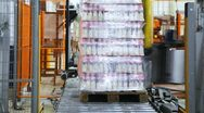 Stock Video Footage of automatic wrapper wraps stretch film bottles of yogurt on pallet