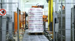 automatic wrapper cuts off end stretch film, and bottles of yogurt on pallet - stock footage