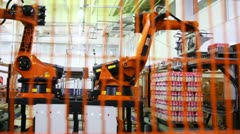 Industrial robot puts yogurt packaging in neat rows on pallet Stock Footage