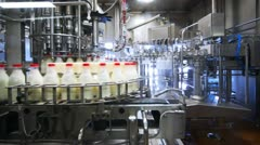 Bottles are washed, dried, filled with milk and close caps in factory conveyor Stock Footage