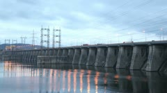 Cars go on bridge in night which is also spillway dike Stock Footage