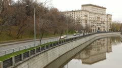 Cars go on river Jauza embankment in front of old building Stock Footage