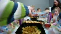 Children celebrate birthday around festive table Stock Footage