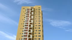 High-rise building of yellow color stands against blue sky - stock footage
