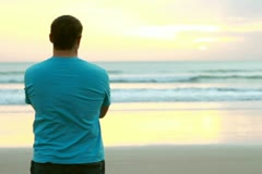 Alone man standing at the beach and looking at sea Stock Footage
