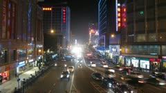 People and cars move along on street night city - stock footage