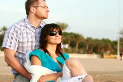 Young happy couple looking at something on the beach Stock Footage
