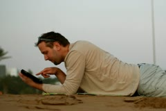 Happy young man with tablet computer lying on the beach Stock Footage
