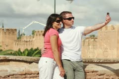 Happy tourist couple taking photo with cellphone near ancient walls Stock Footage