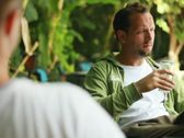 Young happy man talking and drinking beer in bar, outdoors Stock Footage