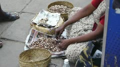 Woman clears the cashew nuts on the street Stock Footage