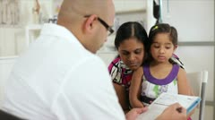Doctor going over the little girl's chart with mother - stock footage