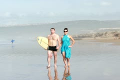 Couple with surfing board walking by the sea, slow motion Stock Footage
