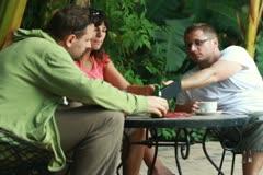 Nuori ystäviä tabletti puhumisen ja juo teetä bar, ulkona Arkistovideo