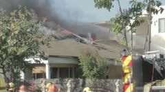 Firefighters hose a flaming and smoky roof at a burning home Stock Footage