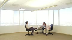 Three businessmen sitting in office chairs while talking Stock Footage