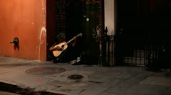 Man sitting in the shadows of street playing guitar Stock Footage