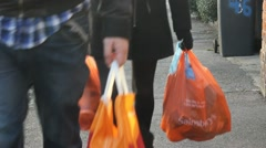 Carrying plastic bags of food. - stock footage