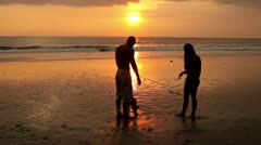 Couple walking on beach with dog at sunset Stock Footage