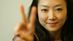 Beautiful young Asian business woman showing V with fingers for victory Stock Footage