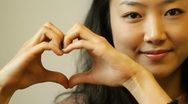 Stock Video Footage of Beautiful young Asian woman makeing heart gesture with hands