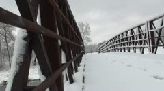 Close up of small trail bridge covered with snow - stock footage