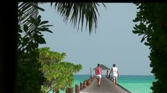 Lovers stroll along the wooden pier into the sea (Maldives) Stock Footage
