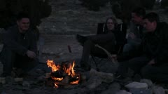 People sitting around a camp fire 2 Stock Footage