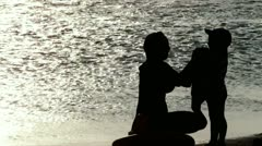 Mom wipes a child after swimming in the sea at sunset Stock Footage