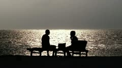family (the lovers) sit by the sea and admire the sunset - stock footage
