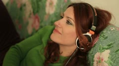 Beautiful woman with headphones, she is listen to the music Stock Footage
