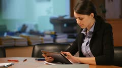 Attractive woman working with the tablet in the office - stock footage