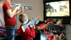 Child and young adult playing video arcade shooting game. Stock Footage