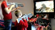 Stock Video Footage of Brothers playing arcade shooting game.