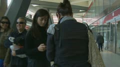 Camera follows two women walking through train station Stock Footage