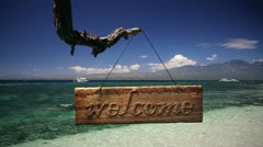 """114 Sign """"Welcome"""" against white sand beach and blue sea Stock Footage"""