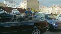 Surburbia, neighbours watch man clean car Stock Footage
