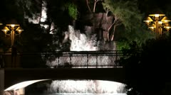 People on a bridge over an artificial waterfall at night Stock Footage