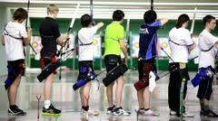 Many young sportsmens archers stand in shooting gallery Stock Footage