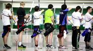 Stock Video Footage of Many young sportsmens archers stand in shooting gallery