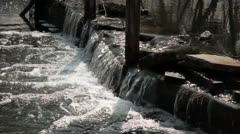 Water flow over big stones on dam in river Stock Footage
