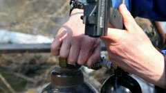 Mans hands operate with gas cylinder and paintball gun Stock Footage