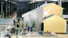 Several workers build house in exhibition hangar Stock Footage