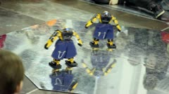 Two toy robots in jeans shorts dance on plate Stock Footage