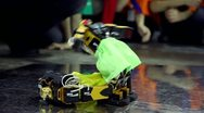Stock Video Footage of Two toy robots in shorts lay on each other, falls and stand up