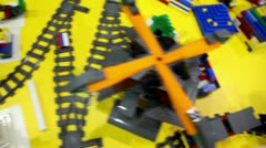 Toy railroad among different objects on yellow surface Stock Footage