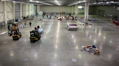 Two loaders stand in empty hangar with several trash piles, people walk around Stock Footage