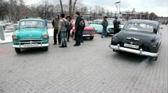 Several people stand near old cars in park at Opening of retro-season Stock Footage