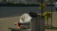 Man sleeping on a street bench Stock Footage