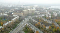 Cars go on highway near to apartment houses in afternoon Stock Footage